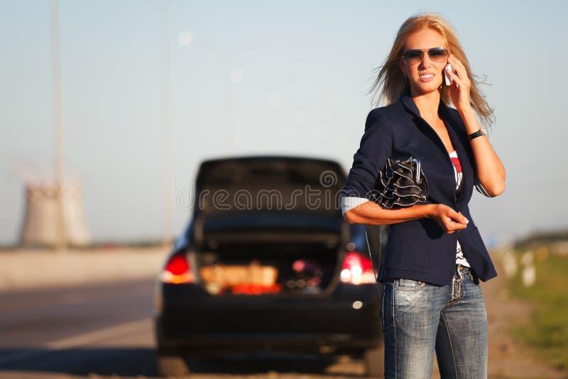 Mulher com um carro quebrado fotografia de stock royalty free