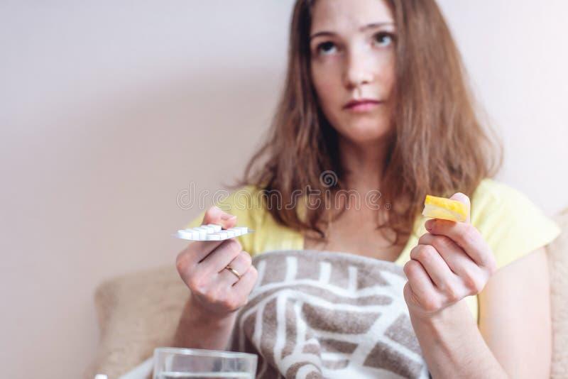 A mulher com um frio escolhe entre comprimidos e vitaminas para o tratamento Gripe sazonal fotografia de stock royalty free