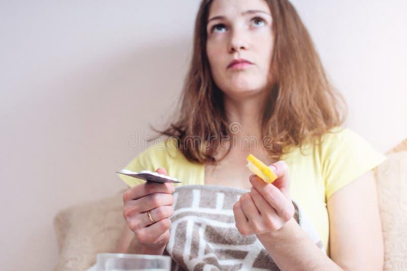 A mulher com um frio escolhe entre comprimidos e vitaminas para o tratamento Gripe sazonal imagem de stock