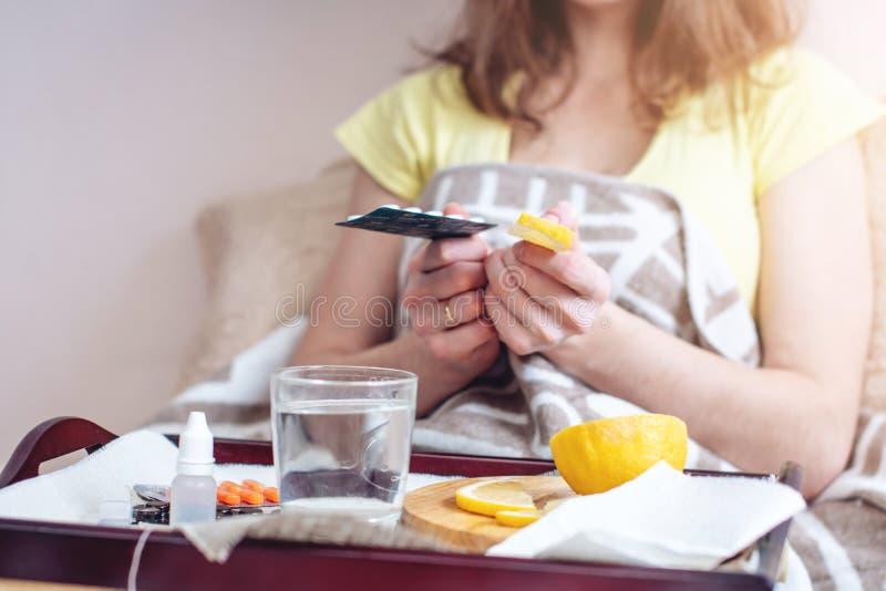 A mulher com um frio escolhe entre comprimidos e vitaminas para o tratamento Gripe sazonal imagens de stock