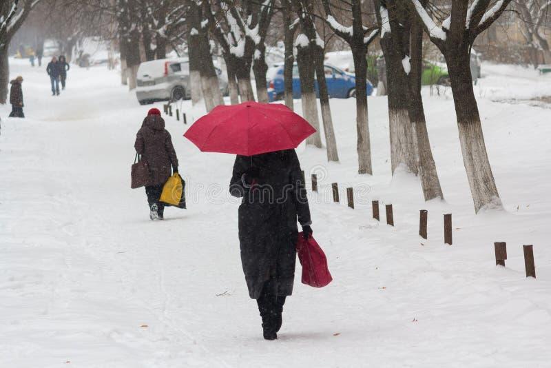 A mulher com um guarda-chuva vermelho está na rua na tempestade da neve fotografia de stock royalty free