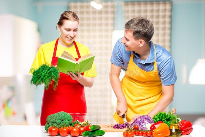 a mulher com um livro da receita, vegetais dos cortes de um homem cozinhou junto uma salada fotografia de stock