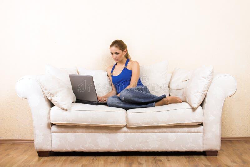 Mulher com um portátil em uma sala de estar fotos de stock royalty free