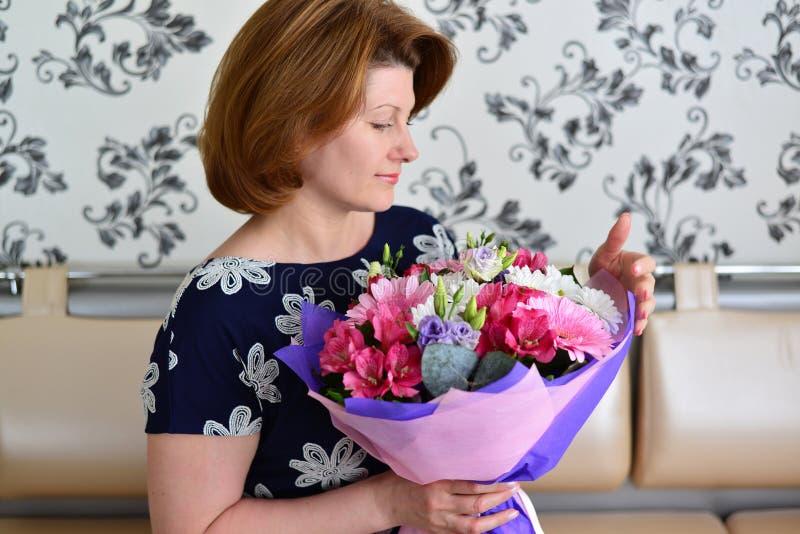 Mulher com um ramalhete das flores na sala fotografia de stock royalty free