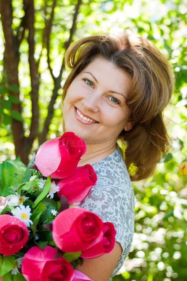 Mulher com um ramalhete das flores no parque do verão fotos de stock