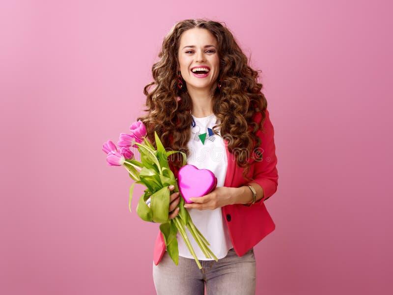 A mulher com um ramalhete das tulipas e um coração deu forma à caixa do chocola foto de stock royalty free