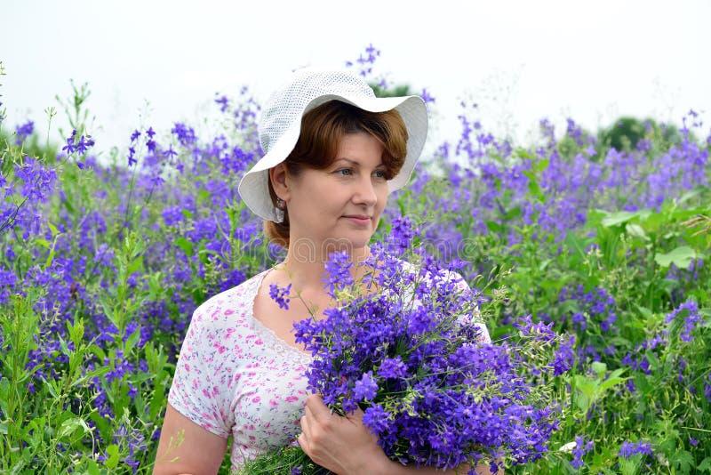 Mulher com um ramalhete de flores selvagens no gramado fotos de stock
