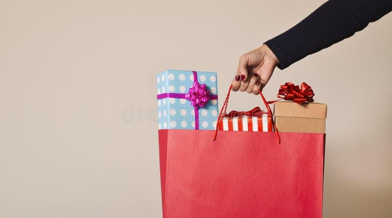 Mulher com um saco de compras completo dos presentes imagens de stock