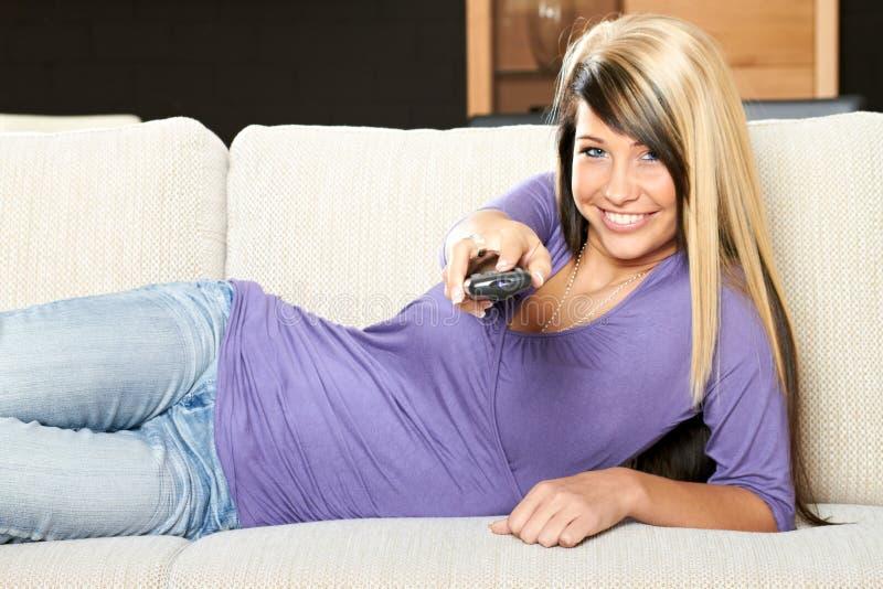 Mulher com um telecontrole da televisão imagens de stock