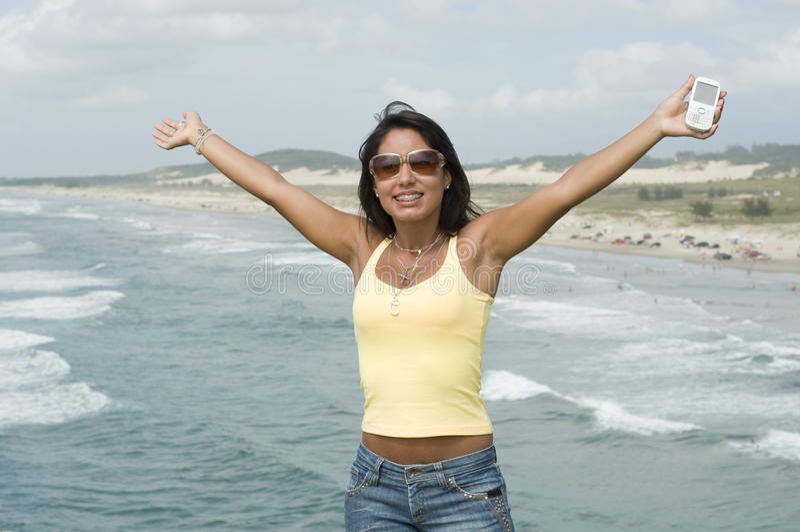 Mulher com um telefone na praia foto de stock royalty free
