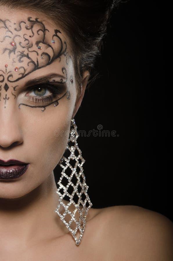 Mulher com um teste padrão do brinco e do laço na cara imagens de stock