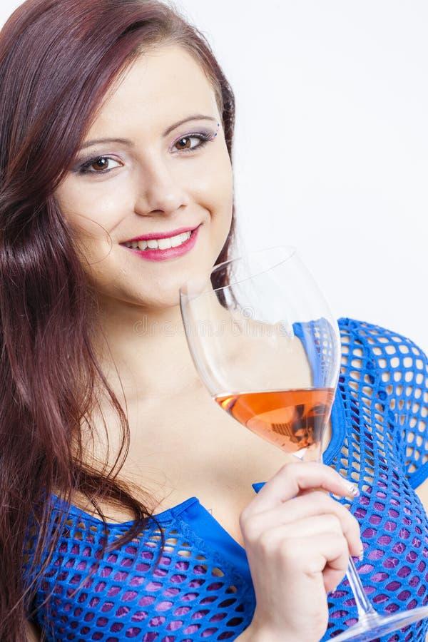 Mulher com um vidro do vinho cor-de-rosa fotografia de stock