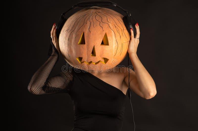 Mulher com uma abóbora na cabeça com música de escuta dos fones de ouvido imagens de stock royalty free