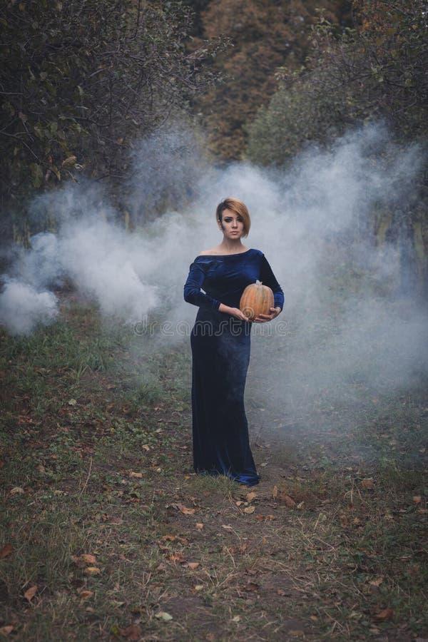 Mulher com uma abóbora na floresta imagem de stock