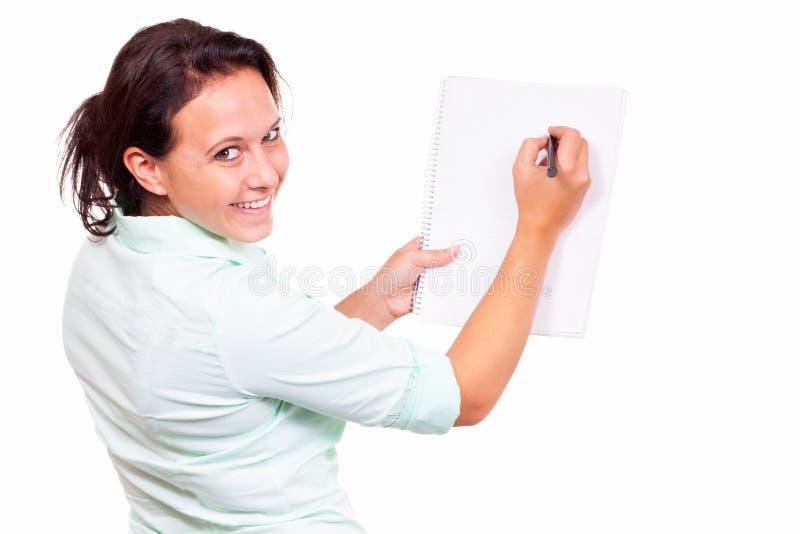 Mulher com uma almofada de escrita imagens de stock