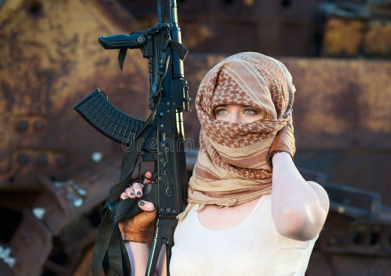 Mulher com uma arma no lenço árabe fotografia de stock