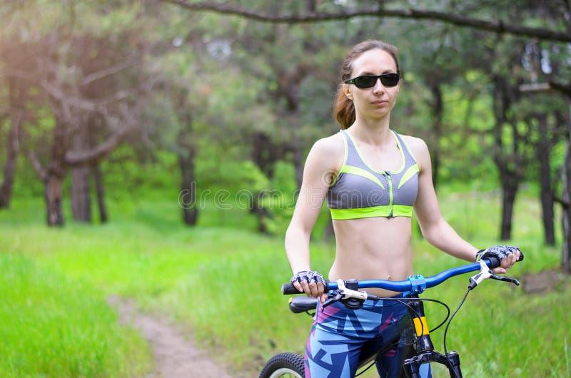 Mulher com uma bicicleta no passeio da bicicleta do verão da floresta, fre dos esportes imagens de stock royalty free