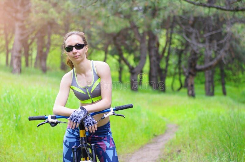 Mulher com uma bicicleta no passeio da bicicleta do verão da floresta, fre dos esportes fotos de stock royalty free