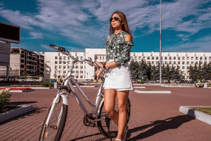 Mulher com uma bicicleta, ver?o na cidade C?u da constru??o do fundo Revestimento verde e short branco da saia Cabelo longo fotografia de stock