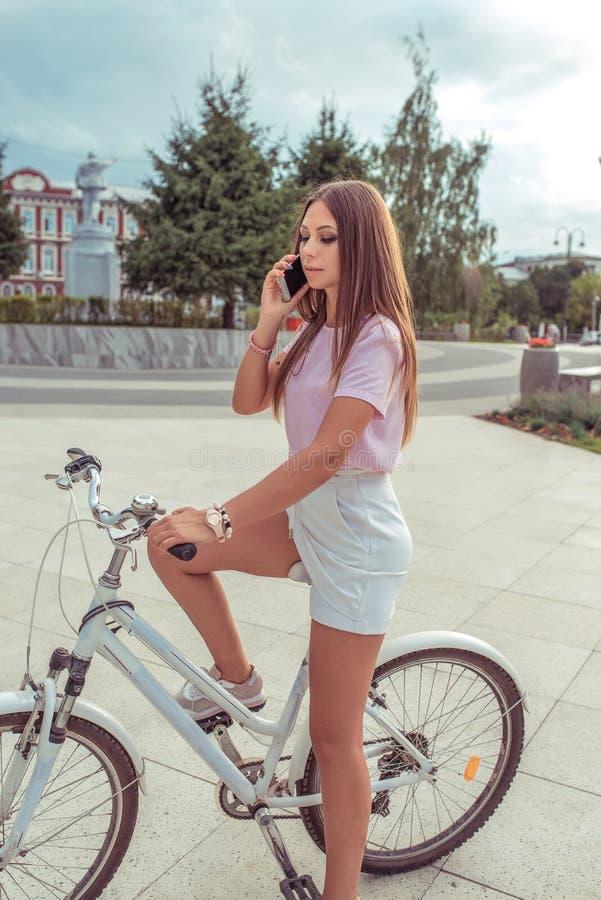 Mulher com uma bicicleta, ver?o na cidade T-shirt cor-de-rosa e short branco da saia Cabelo longo Chamadas pelo telefone, em linh imagens de stock royalty free