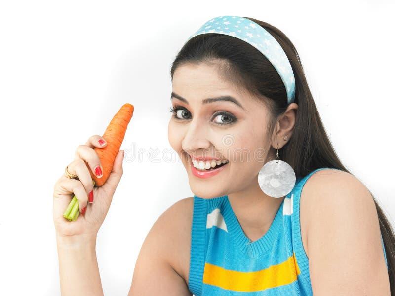 Mulher com uma cenoura alaranjada fresca foto de stock