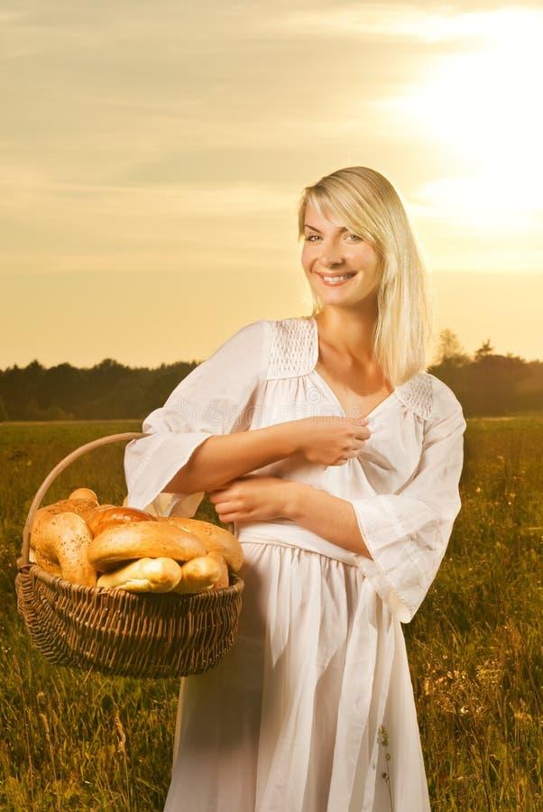 Mulher com uma cesta do pão imagens de stock royalty free