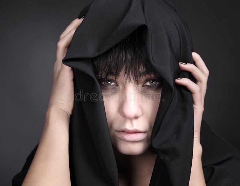 Mulher com uma face pálida no preto imagens de stock