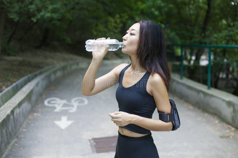 Mulher com uma figura perfeita que faz esportes, aptidão, água potável imagem de stock royalty free