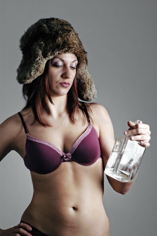 Mulher com uma garrafa da vodca fotos de stock