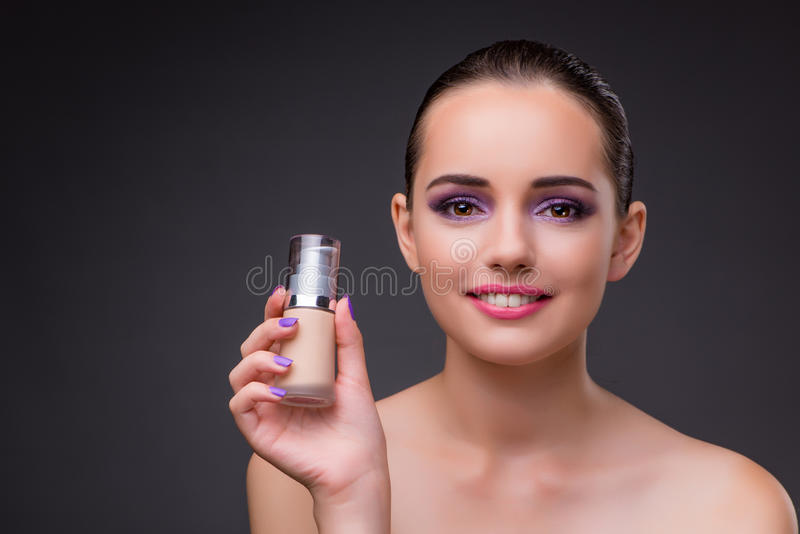 A mulher com uma garrafa do creme imagem de stock royalty free