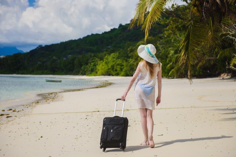 Mulher com uma mala de viagem em uma praia tropical imagem de stock