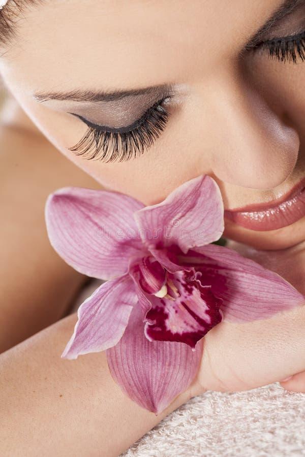Download Mulher com uma orquídea foto de stock. Imagem de modelo - 65577452