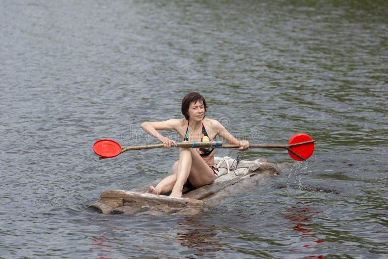 Mulher com uma pá em uma jangada de madeira foto de stock royalty free