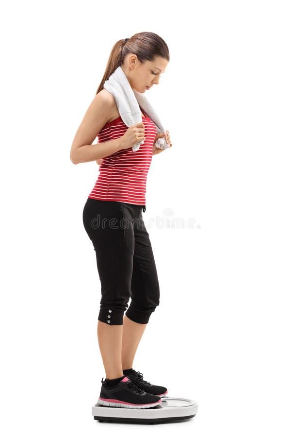 Mulher com uma toalha que está em uma escala do peso fotografia de stock