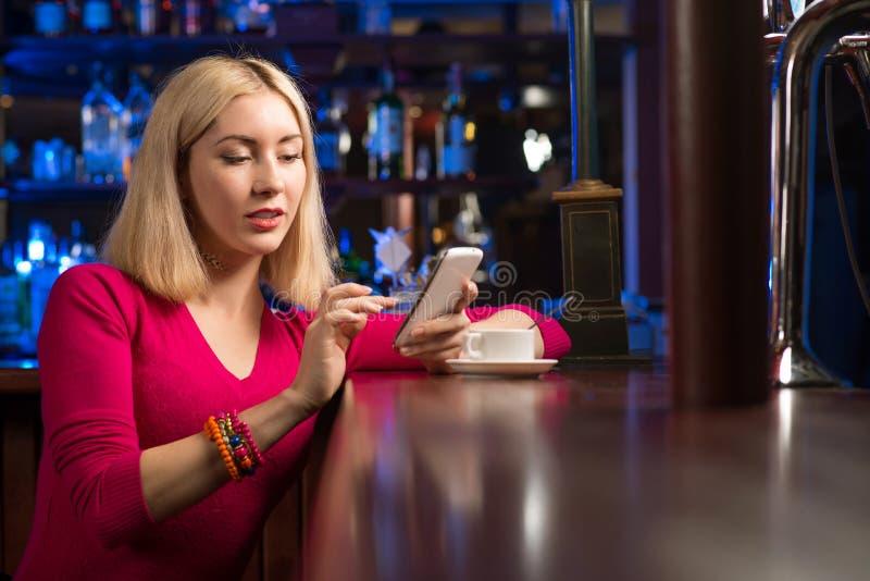 Mulher com uma xícara de café e um telefone celular fotografia de stock