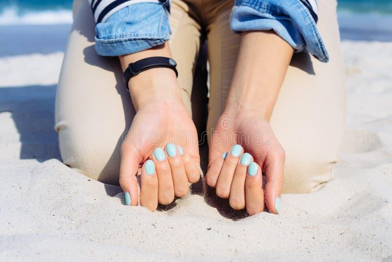 Mulher com verniz para as unhas azul nas mãos que sentam-se na areia da praia fotos de stock