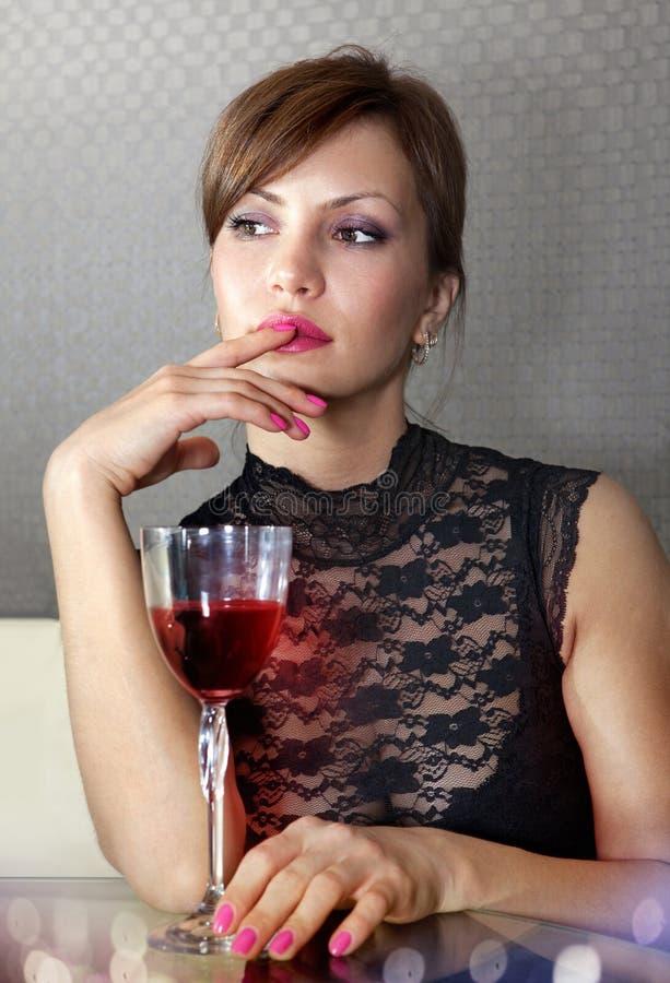 Mulher com vidro do ll do vinho fotografia de stock royalty free