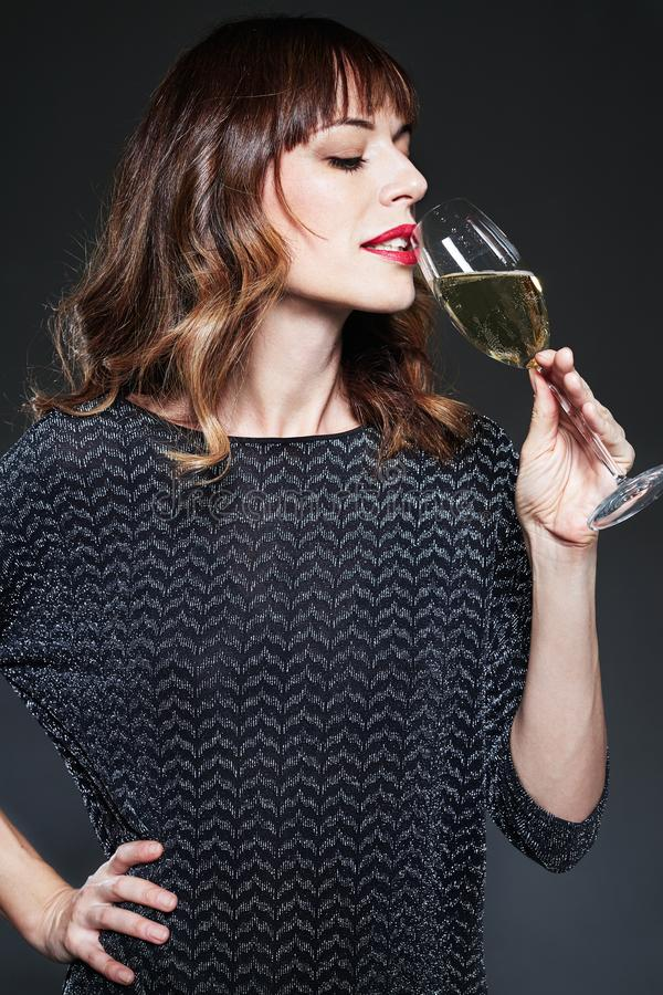Mulher com vidro do vinho espumante bebendo do champanhe no fundo escuro Senhora com cabelo encaracolado longo que comemora Retra foto de stock