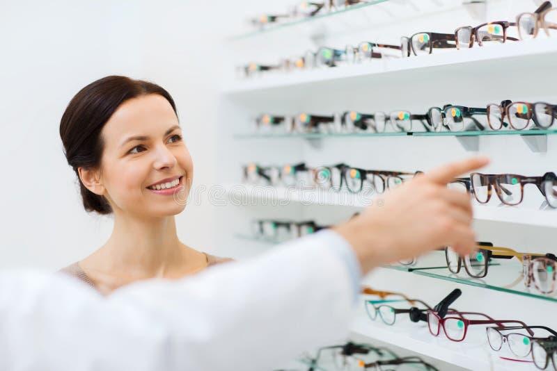 Mulher com vidros e ótico na loja do sistema ótico fotografia de stock