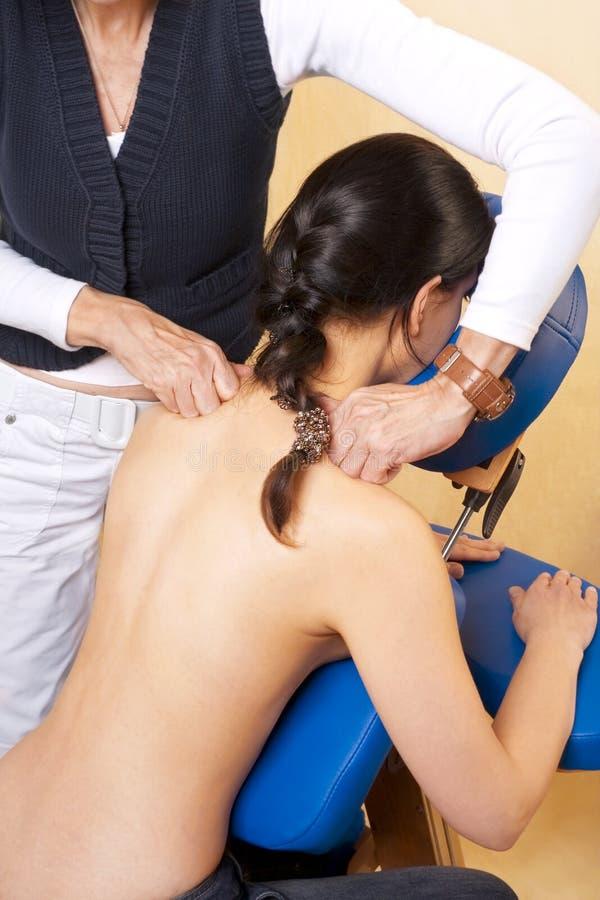 A mulher começ a massagem, acupressure em seu ombro fotos de stock