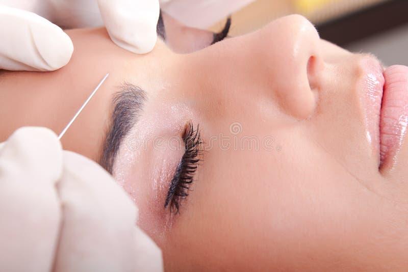 A mulher começ uma injeção do botox
