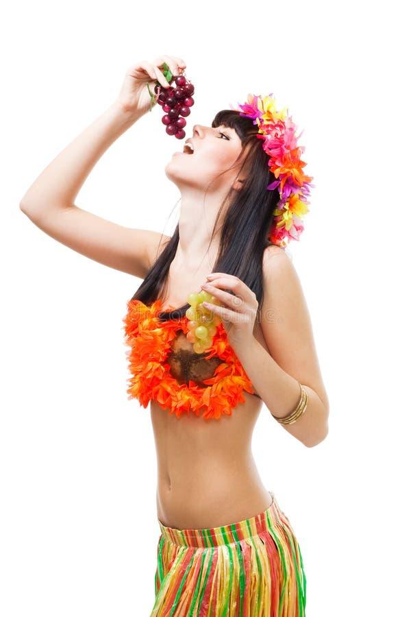 A mulher come as uvas que desgastam o biquini feito das flores fotografia de stock royalty free