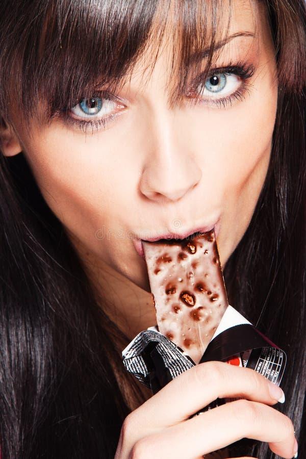 A mulher come a barra de chocolate imagem de stock