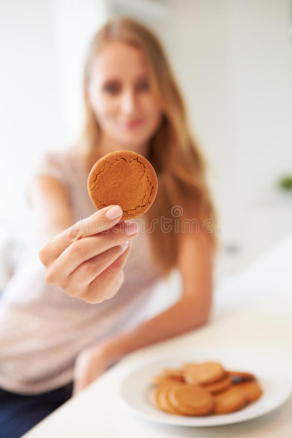 A mulher come Ginger Biscuit To Stop Nausea da doença de manhã foto de stock