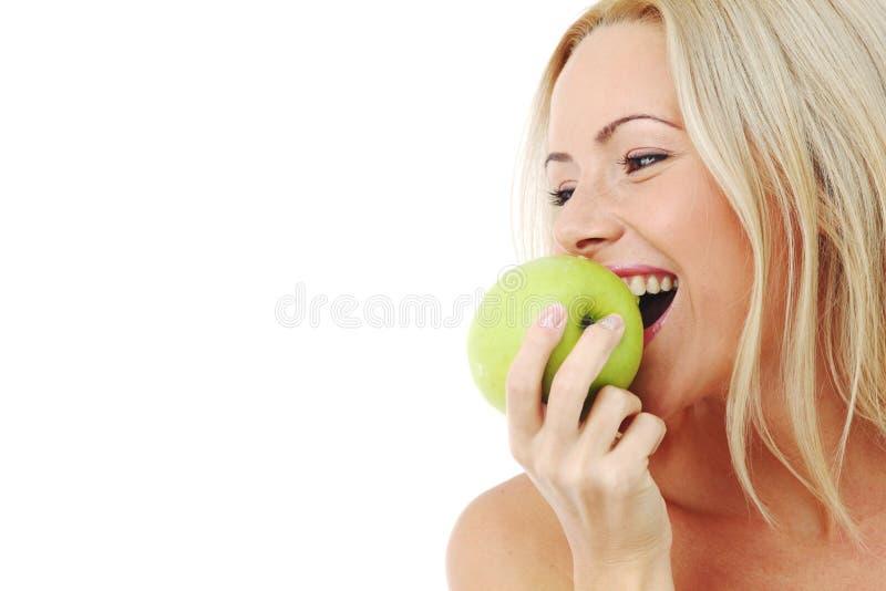 A mulher come a maçã verde fotografia de stock royalty free
