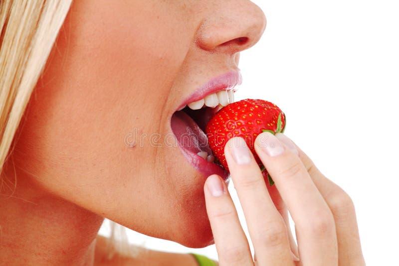 A mulher come a morango imagem de stock