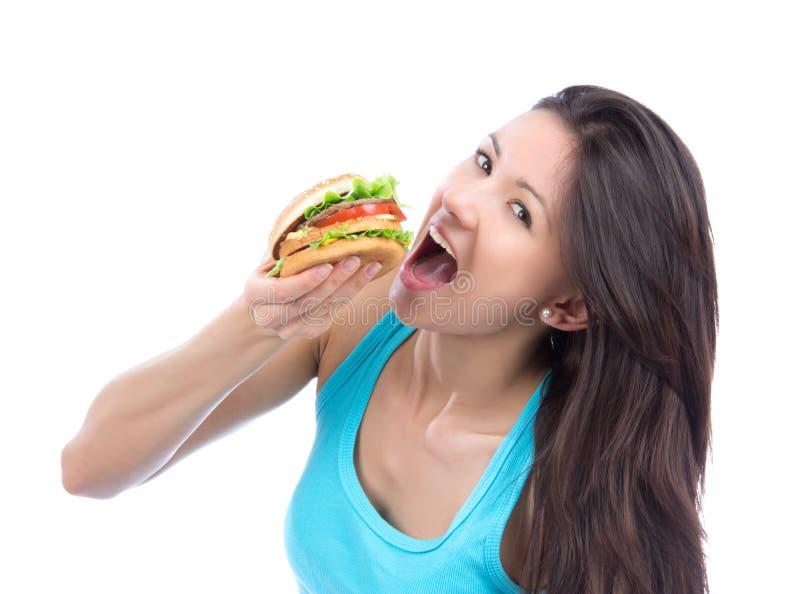 A mulher come o hamburguer insalubre do fast food imagem de stock royalty free