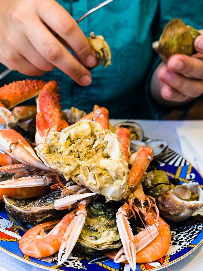 A mulher come o marisco no restaurante local dos peixes fotografia de stock royalty free