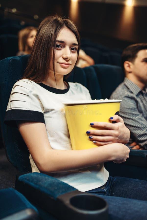 A mulher come a pipoca ao olhar o filme no cinema imagem de stock royalty free