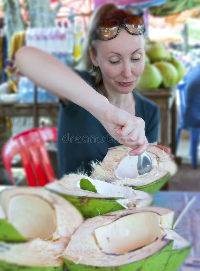 A mulher come a polpa do coco no café da borda da estrada da rua fotos de stock